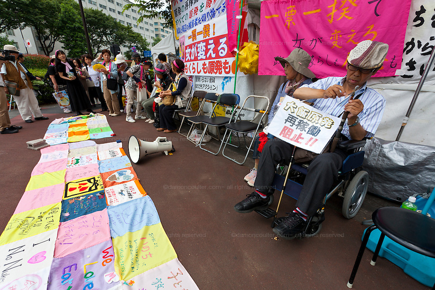 A man in a wheelchair and women protest outside METI (Ministry of Economy, Trade and Industry) in Tokyo, Japan. Friday June 29th 2012. About 400 protesters campaigned the restarting of the Oi nuclear power-station and the policy of Prime-Minister Noda to restart Japan's nuclear power generation programme which has been stalled since the earthquake and tsunami of March 11th 2011 caused meltdown and radiation leaks at the Fukushima Daichi Nuclear power-plant.