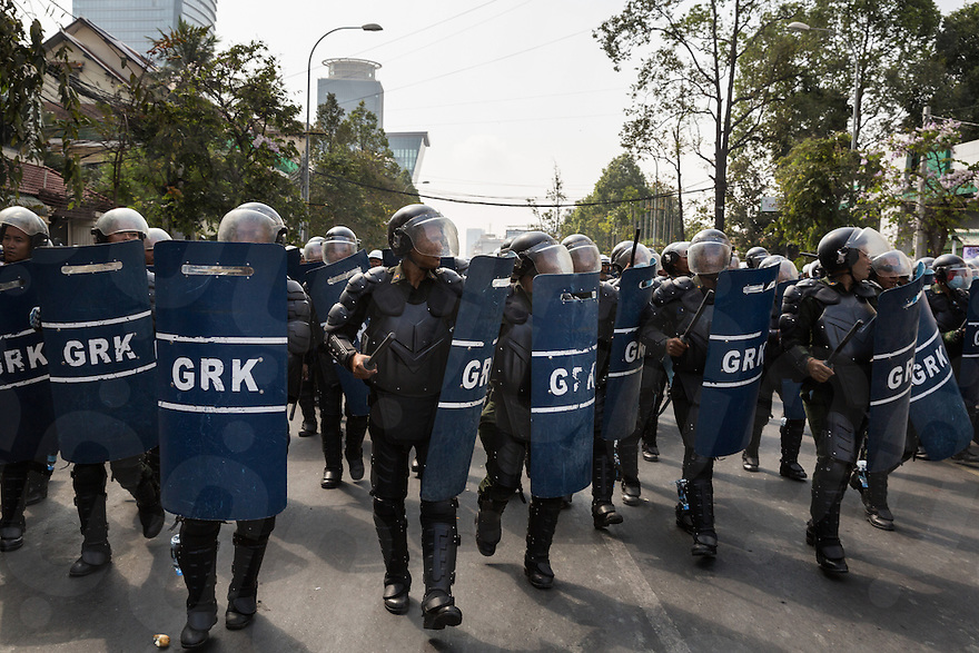 January 27, 2014 - Phnom Penh, Cambodia. Riot police storm a protest led by Mam Sonando (not pictured). Sonando and supporters gathered in front of the Ministry of Information to ask for a T.V. station and wider bandwidth for his Beehive radio station. © Nicolas Axelrod / Ruom