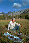 "Billy Butler shows off his catch of fish from Hutchings Creek.<br /> <br /> In August of 1987, the family and friends of Ansel Adams made a trip to Mount Ansel Adams to honor Ansel by putting his ashes on the mountain.  Leading the trip were Dr. Michael Adams and his wife, Jeanne, their son, Matthew, and daughter, Sarah.  Also in the group were Ansel's daughter, Anne Adams Helms, and her husband, Ken Helms, and Anne's daughters, Virginia (Ginny) Mayhew and Sylvia Mayhew Desin, and Sylvia's husband, Greg Desin.  Other members of the trip were Roger and Mitzi Hall, Matt Weston, Mrs. Desin (Greg's mother), and Billy Butler.  The Adams family invited me along with Leo Stutzin (Modesto Bee reporter) and my eldest son, Aaron Golub.  <br /> <br /> With some of us on horseback and others on foot, we began the hike at Tuolumne High Sierra Camp and headed to Vogelsang High Sierra Camp for the first night out.  The second day, we began by climbing through Vogelsang Pass, then descended by switchback down to Lewis Creek.  After climbing up from the creek we hiked by the Cony Crags before descending into the Lyell Fork of the Merced River ending up near Hutchings Creek at what is now referred to as the Ansel Adams Camp.  <br /> <br /> This camp was originally known generically as a Sierra Club Camp, but has more recently been referred to as Ansel Adams Camp because in 1934, Ansel led a Sierra Club outing to the Lyell Fork of the Merced River.  After the group climbed the then-unnamed peak that Adams called ""The Tower in Lyell Fork,"" they gathered around the campfire and agreed that the peak should bear Ansel's name.  The U.S. Geological Survey does not, however, permit naming features for living individuals, so the peak did not officially become Mt. Ansel Adams until 1985, one year and one day after his death.  Photo by Al Golub/Golub Photography"