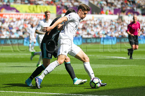 May 21st 2017, Liberty Stadium, Swansea Wales;  EPL Premier league football, Swansea versus West Bromwich Albion; Federico Fernandez of Swansea City (R) holds the ball up while under pressure from Claudio Yacob of West Bromwich Albion (L)