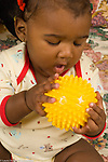 6 month old baby girl Hispanic Dominican American closeup holding bumpy toy ball with both hands interested looking at it vertical