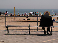 Brooklyn, New York - 6 June 2009 - Man sits on a bench on the Coney Island boardwalk.