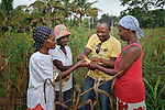 Alphonse Papouloute (second from right), an agronomist with the United Methodist Committee on Relief (UMCOR), talks with (left to right) Terese Midi, Amide Milfort, and Sonia Jean Louis about how to increase their production of corn. The women are farmers in the rural Haitian village of Mizak.