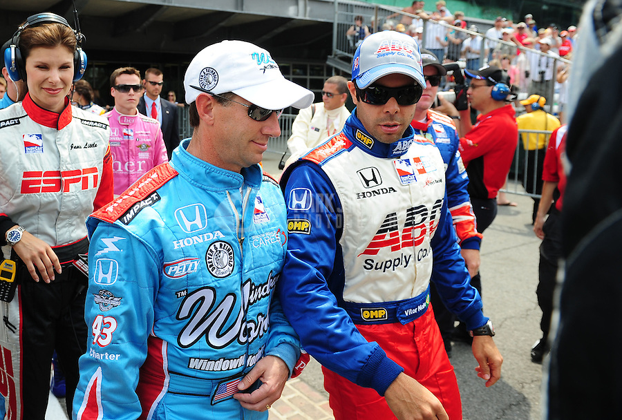 May 24, 2009; Indianapolis, IN, USA; IRL driver Vitor Meira (right) talks with John Andretti prior to the 93rd running of the Indianapolis 500 at Indianapolis Motor Speedway.  Mandatory Credit: Mark J. Rebilas-