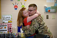 NWA Democrat-Gazette/BEN GOFF @NWABENGOFF<br /> Myra Cooper, 7, jumps into the arms of her father Staff Sgt. William Cooper of Bentonville Monday, May 8, 2017, as he arrived to be the surprise 'Mystery Reader' in her first grade classroom at Apple Glen Elementary School in Bentonville. Each week a parent comes in as a 'Mystery Reader' for their child's classroom at the school, with students receiving clues as to who it will be throughout the week. This week Myra was surprised by her father, who has been away from his family for over a year on deployment to Kuwait with the U.S. Army 77th Combat Aviation Brigade. Staff Sgt. Cooper read to the class from 'Harold and the Purple Crayon' by Crockett Johnson before taking Myra and the rest of their family to spend the day a the nearby Scott Family Amazeum.