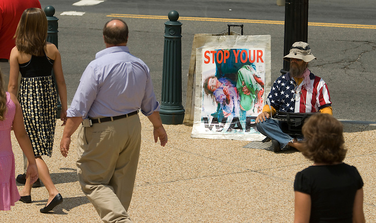 A war protester sits on the sidewalk outside the Cannon House Office Building June 189, 2008.