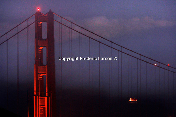 The evening fog sits on top of the city as the Golden Gate Bridge frames the bay... ...