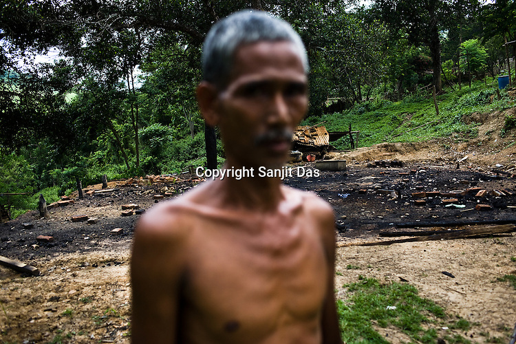 One of the victims of ethnic violence, Kailash poses in front of his burnt house in Jorai village. On 8th May 200, suspected Zeme Naga groups attacked Jorai, a Dimasa village. They burnt down 10 out of 13 houses but spared the school and the community centre, where most of the families are taking shelter. Ethnic clashes are regularly taking place between Zeme Nagas and the Dimasa tribe in North Cachar Hills in Assam, India.