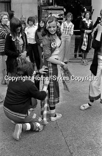 Bay City Roller Fans pop group leave pop concert at Hammersmith Odeon, west London 1975. They are wearing the Bay City Roller tartan fashion