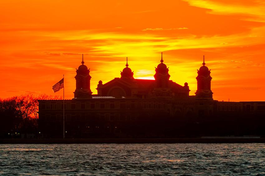 Ellis Island silhouetted at sunset, New York harbor, New York, New York USA.
