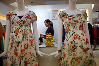 A shop clerk fetches a dress for a customer at the Orient department store in Nanjing, China.