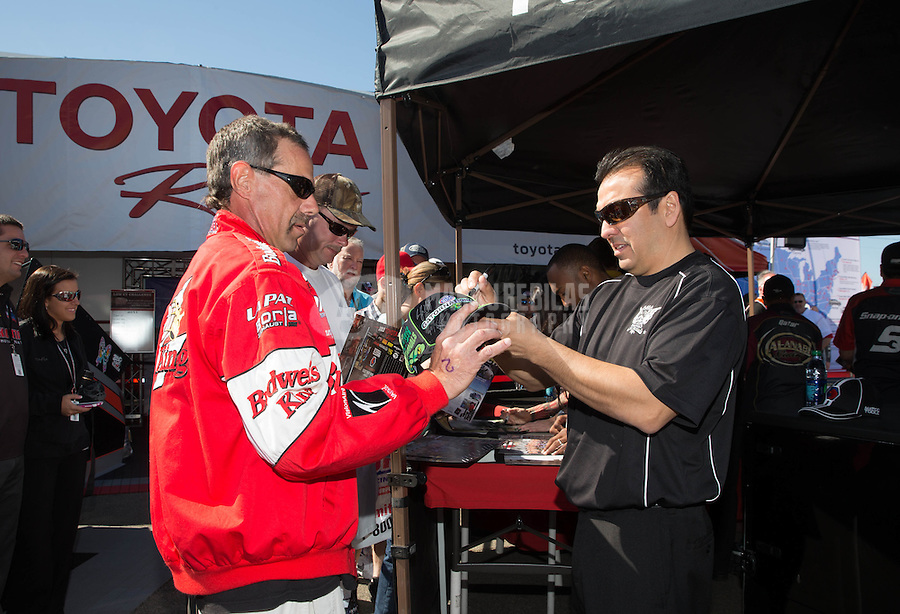 Mar. 16, 2013; Gainesville, FL, USA; NHRA funny car driver Tony Pedregon autographs a fans hat at an autograph session in the Toyota display during qualifying for the Gatornationals at Auto-Plus Raceway at Gainesville. Mandatory Credit: Mark J. Rebilas-