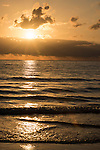 Port Douglas, Australia; the sun rises through cloud formations over the Coral Sea