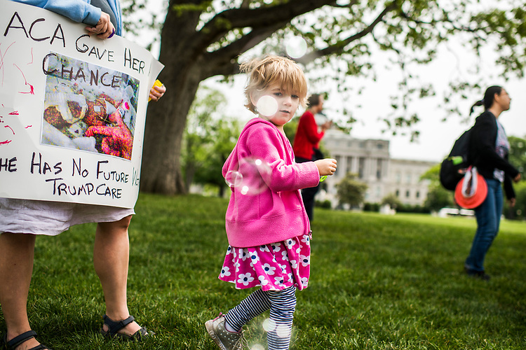 UNITED STATES - MAY 4: Charlie Wood, 4, of Charlottesville, Va., plays with bubbles during rally on the East Front lawn of the Capitol to oppose the House Republicans' bill to repeal and replace the Affordable Care Act on May 4, 2017. She was born 3 1/2 months earlier and her mother Rebecca, at left, holding a picture of Charlie in the hospital, fears changes to the ACA will negatively effect her current care. (Photo By Tom Williams/CQ Roll Call)
