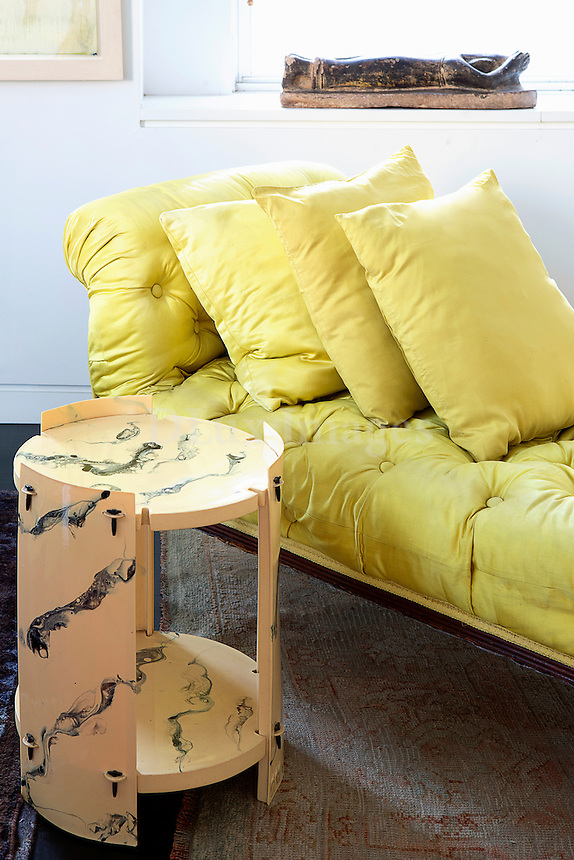 Modern yellow chaise lounge and side table