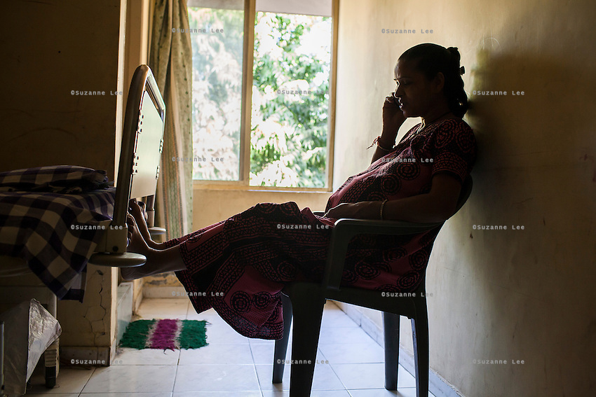 A surrogate passes her time chatting on her mobile phone in the surrogates hostel on the 3rd floor of Dr. Nayana Patel's Akanksha IVF and surrogacy center in Anand, Gujarat, India on 11th December 2012. Photo by Suzanne Lee / Marie-Claire France