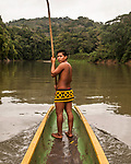 An indigenous Embera man in traditional dress stands in the front of the dugout canoe or cayuco with a long pole to move the boat in shallow water.  Panama Chagres National Park