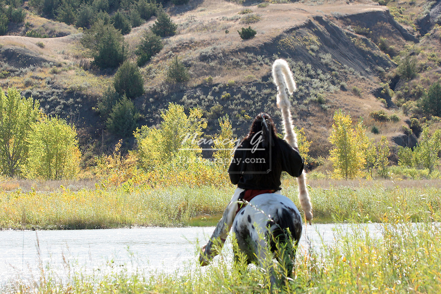 A Native American Sioux Indian on horseback on the edge of a river in South Dakota.  Indian not in focus, but focused on the back hills