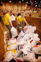 Tuesday February 16, 2010.  Volunteers move Karin Hendrickson's dog food bags from her trailer to begin the weigh, tag and sort process at the musher's food drop.