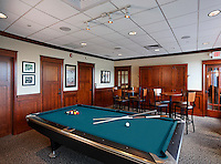 Arts & Crafts style wood panelled game room at private club. Pool table in foreground.