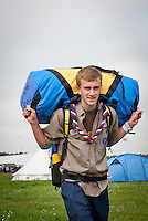 A Scout from the UK is carrying his bag on the back  to his campsite