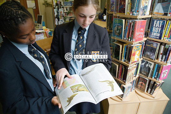 Secondary school students looking at books in the school library,