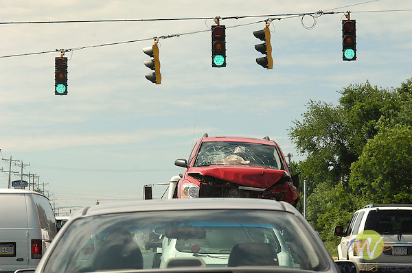Wrecked car in traffic line near Philadelphia with three green traffic lights.