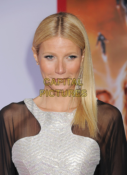 "Gwyneth Paltrow, wearing Antonio Berardi.arriving at the Los Angeles Premiere of ""Iron Man 3"" at El Capitan Theatre in Hollywood, California, USA, .April 24, 2013. .portrait headshot beauty make-up white black sheer dress  see through thru silver silver trim  smiling earring dangly funny face .CAP/ROT/TM.©TM/Roth Stock/Capital Pictures"