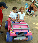 BABYLON, NY-MONDAY, AUGUST 13, 2007: Emma Valle,4, of Babylon gives Justin Alvarez,4 of Deer Park, a ride in her toy Jeep and friend Joseph D'Amato 5, also of Deer Park watches at left, at Argyle Lake Park in Babylon on Monday August 13, 2007. <br /> <br /> Newsday / Jim Peppler