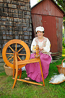 Colonial wife at spinning wheel uses short draw technique to create yarn from combed sheep's wool fibers at the Nathan Hale Homestead during a Revolutionary War encampment and muster, Coventry, Connecticut, USA.