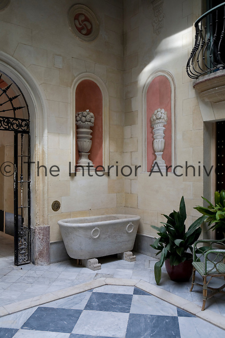 The ground floor courtyard of a Spanish town house, paved with a chequerboard of marble surrounded by terracotta tiles