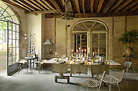 A table is laid for dinner in the 18th century orangery with its original beamed ceiling and restored stone walls