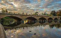 Sunset photograph of the Serpentine Bridge which is located in Hyde Park in London England. <br /> The evening lighting was spectacular. Colourful reflections from the clouds was reflecting onto the water below as the pedestrians on the bridge enjoyed the view of the last minutes of daylight.