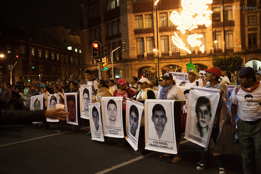 Parents and relatives of the 43 missing students from Ayotzinapa's teacher training college, hold images of the missing students, during a massive march  in Mexico City, Mexico on November 20, 2014. Caravans of students and family members of 43 missing Ayotzinapa's students converged on the capital after several days crisscrossing the country.Parents of the 43 missing students still do not believe the official line that the young men are all dead. Criticism of the government has intensified in Mexico and the country has been convulsed by protests. Many are demanding justice and that the search for the 43 missing students continue until there is concrete evidence to the contrary. Mexico officially lists more than 20 thousand people as having gone missing since the start of the country's drug war in 2006, and the search for the missing students has turned up other, unrelated mass graves.(Photo by BénédicteDesrus)