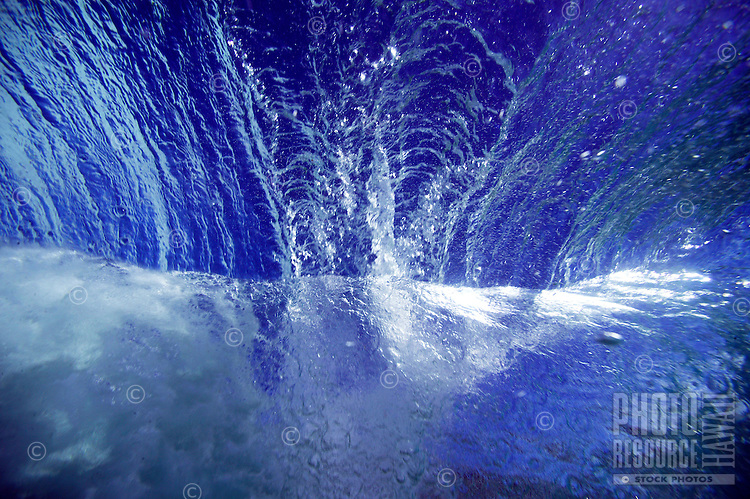 view of sky from under a rolling wave in the clear, blue, tropical ocean water