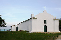 Horses graze in the lee of a whitewashed country church overlooking the beach and the ocean