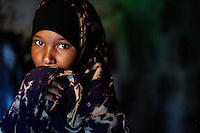 Ester Abdi ali, 14 years old, somali refugee, in her tent in the Kharaz refugee camp In  Yemen on Tuesday November the 27th 2007. THe camp, former military barracks, hosts 9000 somali refugees, most of which have become stable residents, completely dependent on humanitarian donations.  Somalis are allowed to work in Yemen, but due to the a 35% unemployment rate in the country, most of them remain jobless.///..Ever since the collapse of the Siad Barre regime in 1991 Somali men, women and children have been arriving at the port of Bosasso to buy passage in small open fishing boats to Yemen, where they are given automatic political asylum..The  boat trip, costing from 70 to 150 usd per person, can be often fatal due to the roughness of the sea, the overcrowded boats and the merciless of the smugglers..On the night of Nov 29 2007 a small fishing boat while trying to download it's load of refugees a few hundred meters from the Yemeni  shores of Meifa Haja, flipped over and was overwhelmed by the constant waves. of its 130 passengers, only 42 reached the UNHCR ( United Nations High Commissioner for Refugees )  refugee center in Meifa. 30 bodies where recovered the next day.  the rest are still unaccounted for.. UNHCR  estimates more than 80.000 somali refugees live  in the country residing mostly in shanty towns in Sana'a' and Aden.