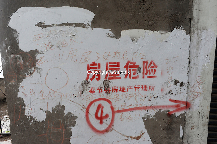 A sign outside blocks of deserted flats states that the flats are dangerous condemned for destruction at Fengie on the Three Gorges Dam. Several of the new cities are suffering from structural damage due to land and earth movements caused by the 400 km Three Gorges reservoir.<br /> <br /> PHOTO BY RICHARD JONES-SINOPIX