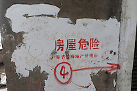 A sign outside blocks of deserted flats states that the flats are dangerous condemned for destruction at Fengie on the Three Gorges Dam. Several of the new cities are suffering from structural damage due to land and earth movements caused by the 400 km Three Gorges reservoir.<br />