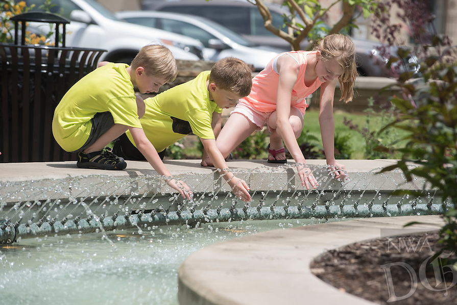 NWA Democrat-Gazette/J.T. WAMPLER Evan Tolliver, 7, (left) and his sister Grace Tolliver, 10 (right), both of Badger Iowa, get wet with Matthew Wright, 7, of Rogers Monday June 13, 2016 at the downtown Bentonville square. The National Weather Service is calling for a chance of rain today ((TUESDAY)) and clear skies through the rest of the week.