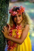 Beautiful young girl dressed up in leis and a muumuu standing by a tree