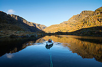 Hikers use rowboat on lake Trolldalsvatnet to access distant mountain peak, Moskenesøy, Lofoten Islands, Norway
