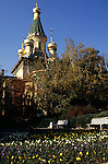 Sofia, Bulgaria; the Russian Church of St Nicholas with gold leaf onion spires and flowers in the foreground.