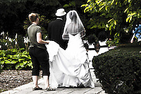 One of the workers at Cantigny Park held the bride's long flowing gown as she walked the cobblestoned path to where the ceremony was being held on the lawn.