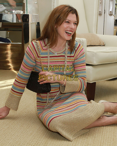 MILLA JOVOVICH .At The Hospitality Suite Hosted by Pacal Mouawad held At The Nivea For Men's Mansion,  Beverly Hills, CA, USA, .14th January 2011..full half length blue pink beige striped dress sweater jumper necklace shoes sitting on floor down black bag smiling  nude cream .CAP/ADM/KB.©Kevan Brooks/AdMedia/Capital Pictures.