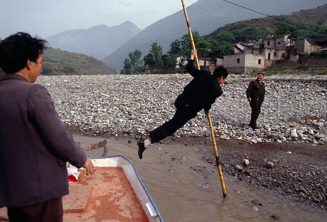 A man in flight pole vaults across to the shore to keep his shoes dry on the Daning River a tributary of the Yangtze River in China