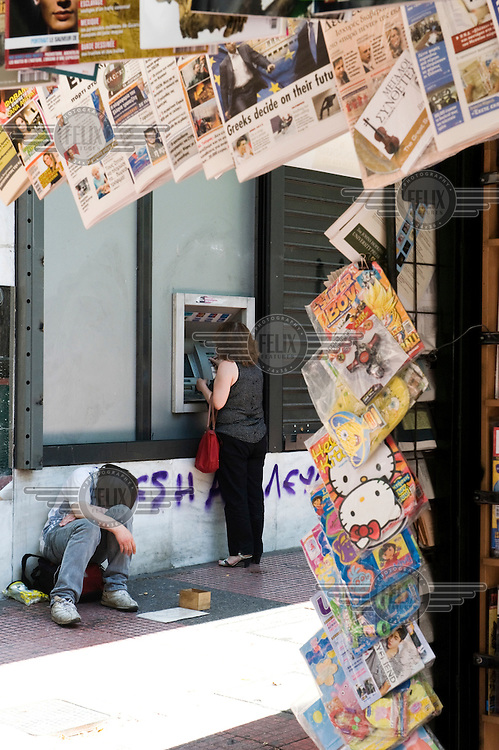 A homeless man sits next to a cash point (ATM) in front of a newspaper kiosk where a woman is withdrawing money on Panepistimiou Street in central Athens. .