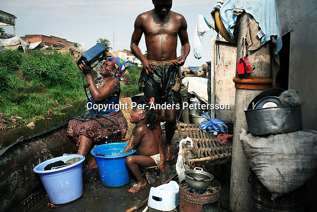 BUMBA, DEMOCRATIC REPUBLIC OF CONGO  MARCH 27: Ngisa Dieu, age 17 (c), a crew member, tries to wash off palm oil from his body, on a boat with destination Kinshasa on March 27, 2006 in Bumba, Congo, DRC. He works with many other young crewmembers without any training and little experience. Ngisa just checked one of the barges tanks filled with palm oil, that the captain suspects are taking in water. Passengers usually sleep in the open, often on top of maize bags or other cargo. The boat carries many animals such as pigs, goats, crocodiles, monkeys, lizards, etc. The Congo River is a lifeline for millions of people, who depend on it for transport and trade. The journey from Kisangani to Kinshasa is about 1750 kilometers, and it takes from 3-7 weeks on the river, depending on the boat. During the Mobuto era, big boats run by the state company ONATRA dominated the traffic on the river. These boats had cabins and restaurants etc. All the boats are now private and are mainly barges that transport goods. The crews sell tickets to passengers who travel in very bad conditions, mixing passengers with animals, goods and only about two toilets for five hundred passengers. The conditions on the boats often resemble conditions in a refugee camp. Congo is planning to hold general elections by July 2006, the first democratic elections in forty years. (Photo by Per-Anders Pettersson)..