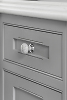 Detail of one of the ceramic, crackle glazed door knobs on the pale grey kitchen cabinetry