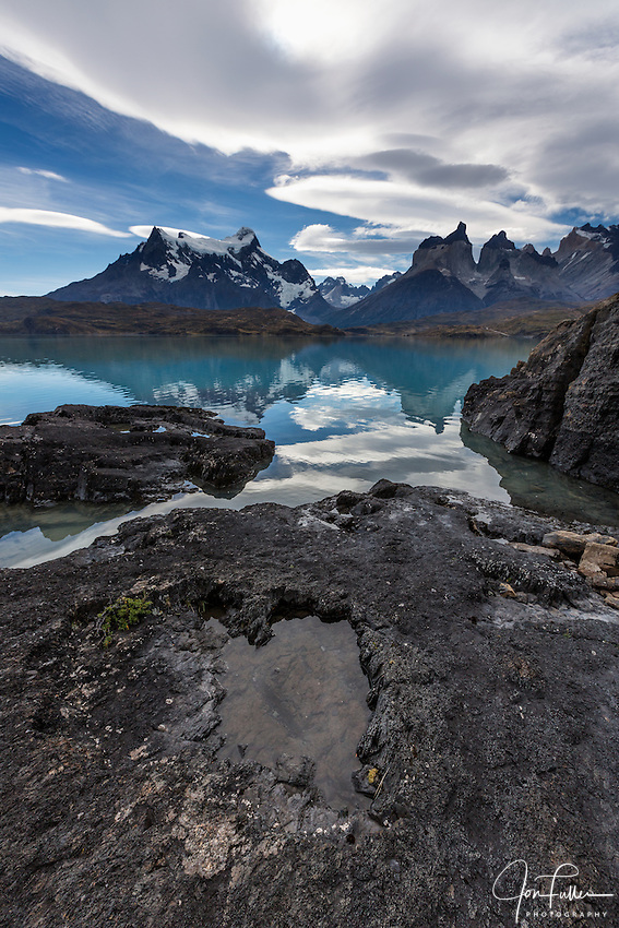 Wide-angle view of the Paine Masif with rocks and Lake Pehoe in the foreground.  From left to right – Cerro Paine Grande, the Cuernos del Paine, or the Horns, and Monte Almirante Nieto.  Torres del Paine National Park in Patagonia, Chile.  A UNESCO World Biosphere Reserve.